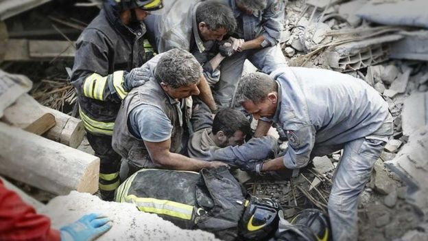 State forestry service photo of rescue workers pulling survivor from rubble