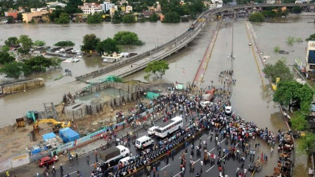 Indian bystanders and travellers gather as floodwaters lap at the end of a highway in Chennai on December 2, 2015.