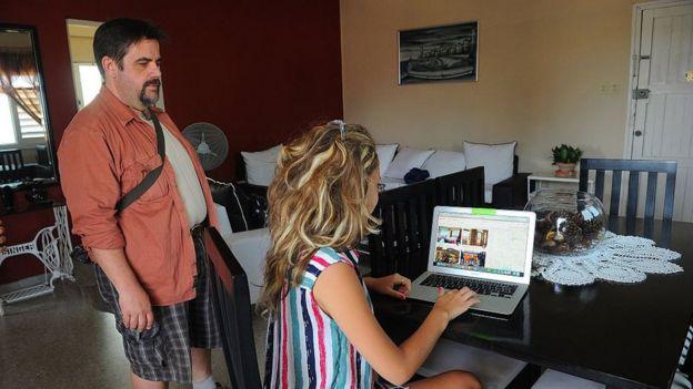 Uma mulher cubana fornece serviços de hospedagem com um laptop em uma casa em Havana