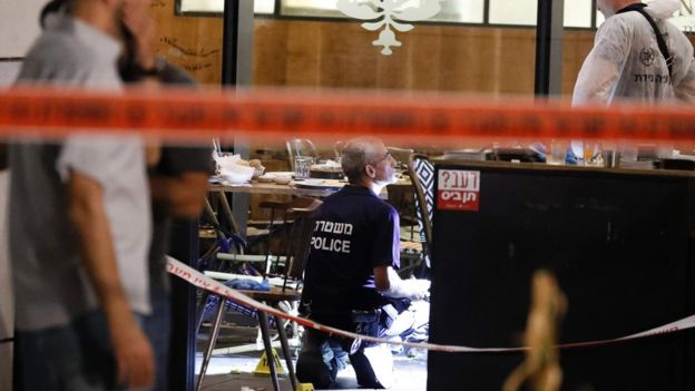 Israeli forensic police inspect a restaurant following a shooting attack at a shopping complex in Tel Aviv on June 8