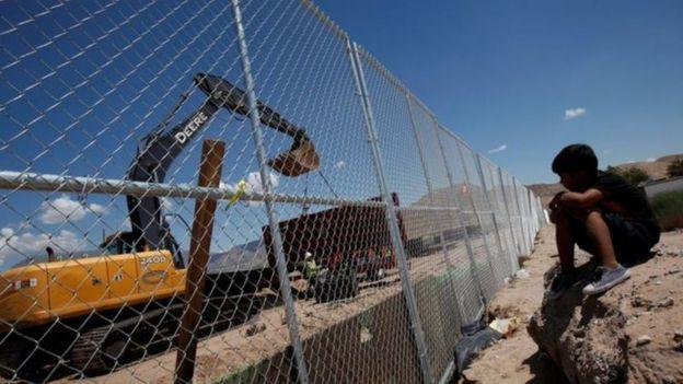 Niño frente a una valla fronteriza en México