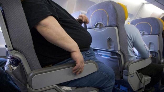 Un pasajero con sobrepeso en el asiento de un avión