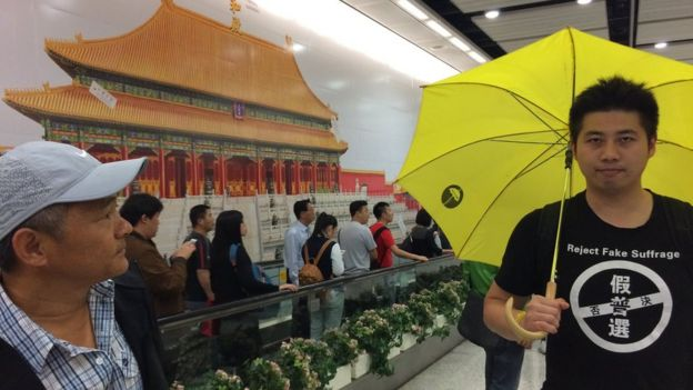 Billboard-sized image of the Forbidden City with passers-by and a man with a yellow umbrella and a T-shirt reading