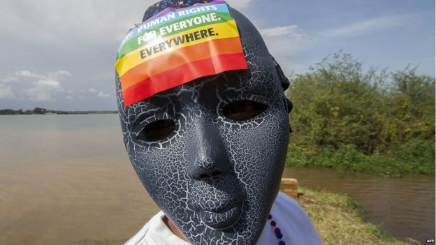 A Ugandan wears a mask with a sticker on at a gay pride rally