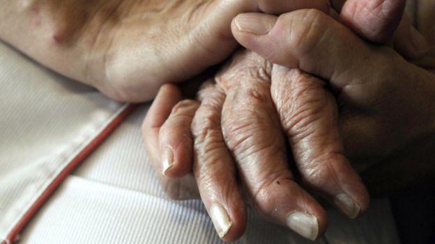 Enfermera sosteniendo las manos de una persona con Alzheimer.