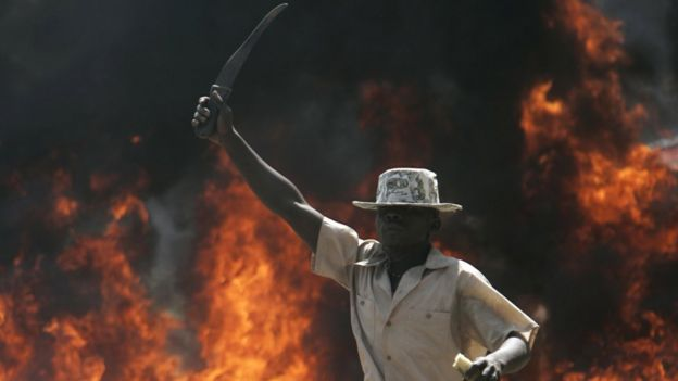 A supporter of the Orange Democratic Party holds up a machete in front of a burning barricade, Saturday, Dec. 29, 2007 during riots in the Kibera slum in Nairobi.