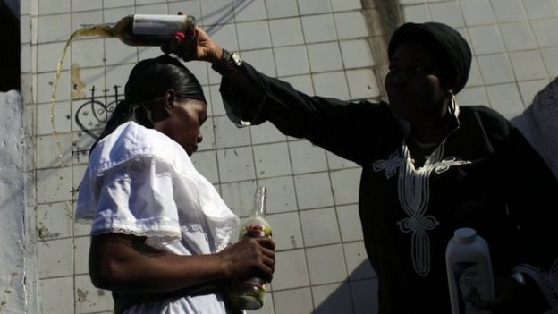 Two women participate in a Voodoo ritual in tribute to Baron Samdi and the Gede family of spirits during Day of the Dead celebrations at the National Cemetery in Port-au-Prince on 1 November, 2015.