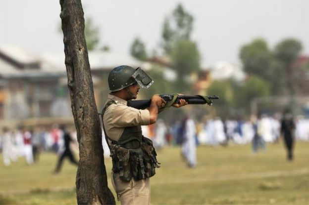 An Indian policeman aim his pellet gun at protesters during a protest in Srinagar, Indian controlled Kashmir, Wednesday, July 6, 2016