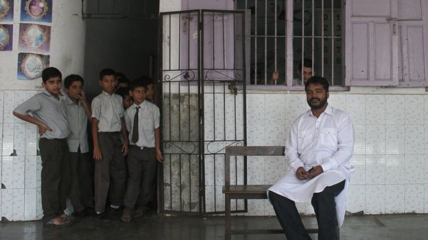 Mr Shaikh sits outside his classroom as his students peep from the door
