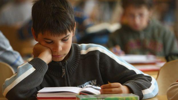 Niño lee un libro en una clase.
