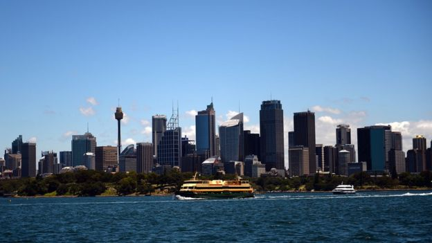 A ferry commutes between Circular Quay and Manly Beach in front of Sydney's central business district skyline