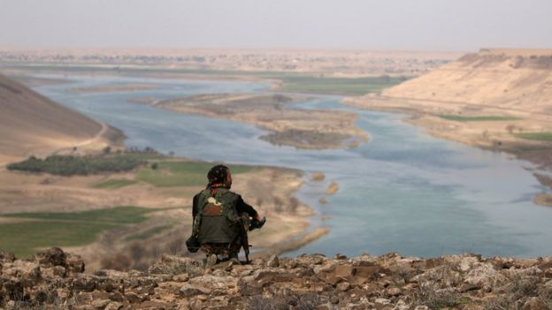 A Syrian Democratic Forces (SDF) fighter rests while looking over the River Euphrates north of Raqqa city, (8 March 2017)