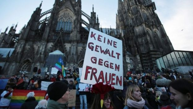 A demonstrator holds a sign in German that reads