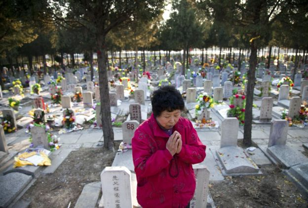 This photo taken on 4 April 2011 shows a Chinese woman praying at the grave of a loved one at the Babaoshan cemetery in Beijing to mark 'Qing Ming' or Tomb Sweeping Da