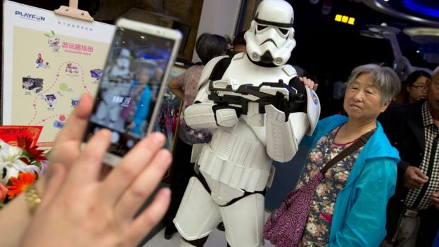 A Chinese woman poses for a smartphone photo with a worker dressed in a storm trooper costume at the Wanda Mall at the Wanda Cultural Tourism City in Nanchang in southeastern China