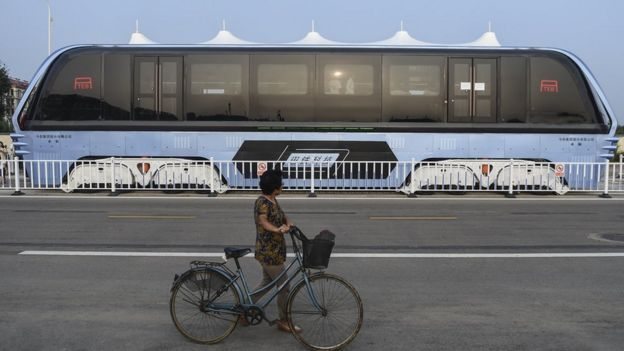 A woman pushes a bicycle looks at the Transit Elevated Bus TEB-1 conduct a test run after it unveiled in Qinhuangdao, north China's Hebei Province