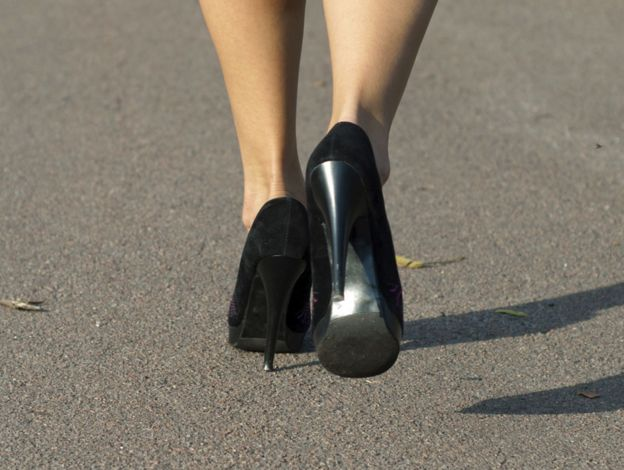 A close up of the feet of a woman walking in heels