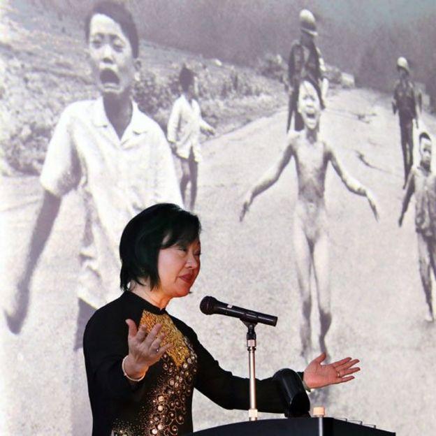 Kim Phuc hablando en una conferencia, detrás de ella está proyectada la foto que tomó Nick Ut en 1972