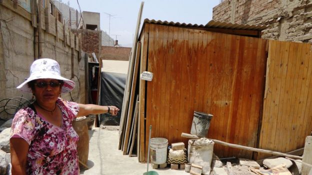 Cristina Inga shows what is left of her house where she lives where she lives with her husband and two children