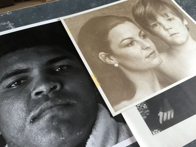 A picture of Stewart's photographs, including one of Muhammad Ali