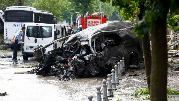 A destroyed van is pictured near a Turkish police bus which was targeted in a bomb attack in a central Istanbul district