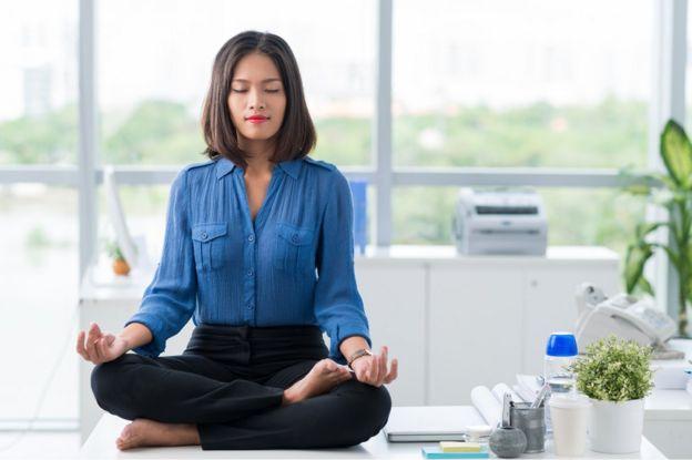 Mulher meditando na mesa de trabalho