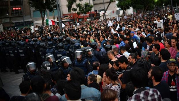 Riot police form a line to hold back the demonstration in Mexico City