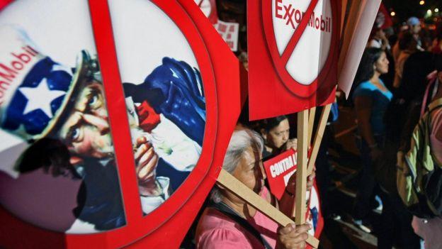 Una manifestante con un cartel contra ExxonMobil