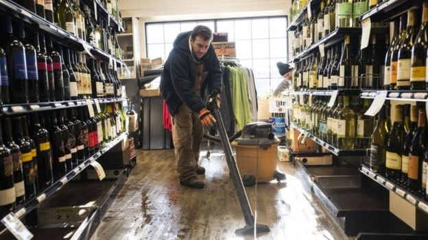 An employee of a liquor store cleans the floor after it flooded following a blizzard on in Stone Harbor, New Jersey (24 January 2016)