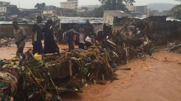 People walking across a flooded road
