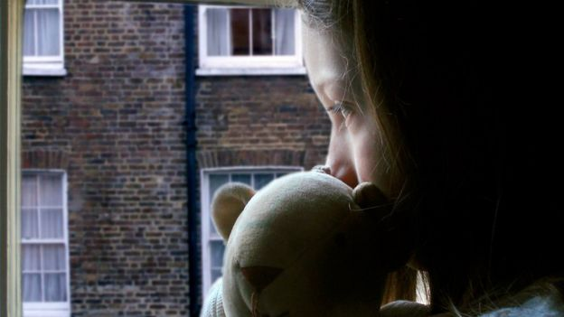 Young girl looking out of a window holding a teddy bear.