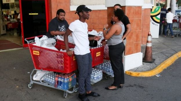 Jamaicans stand next to shopping carts filled with bottled water and other items outside a supermarket in Kingston (30 September 2016)