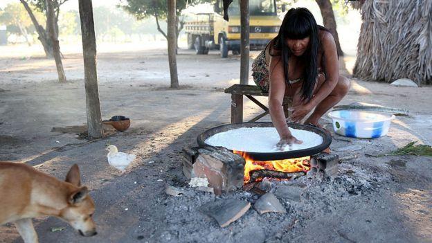 Una indígena cocina un casabe