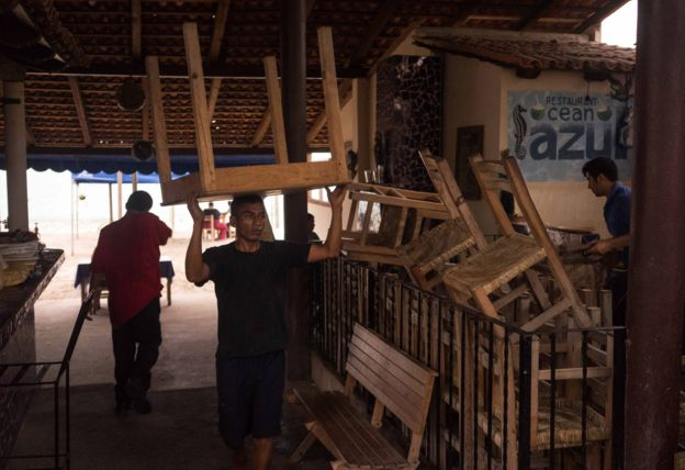 A worker carries a table at a seaside restaurant preparing for the arrival of hurricane Patricia in the Pacific resort city of Puerto Vallarta, Mexico, Thursday, Oct. 22, 2015