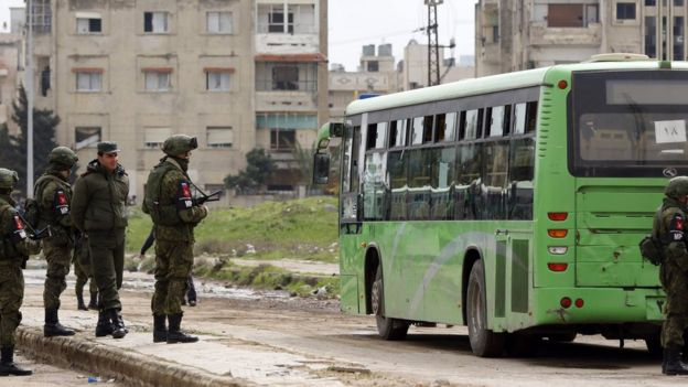 Russian Military police stand guard as a bus drives towards the rebel-held Waer neighbourhood in the central Syrian city of Homs, to transport opposition fighters and their families, on March 18, 2017