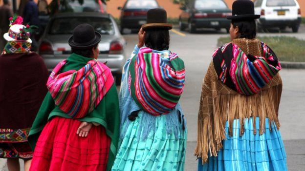 Peruanas caminando en la ciudad con faldas y ponchos de la sierra.