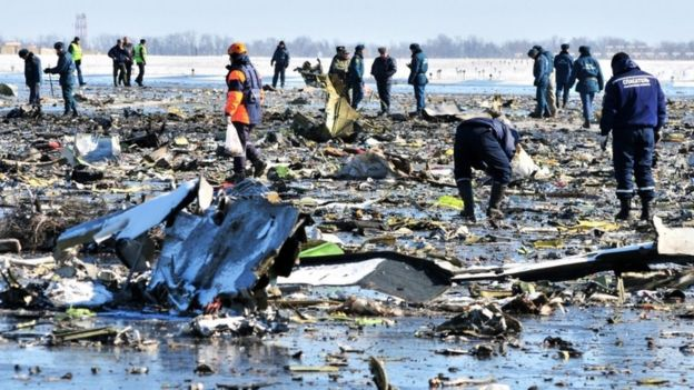 Russian investigators and policemen inspect the crash site of a Boeing 737-800 FlyDubai plane at Rostov-on-Don airport