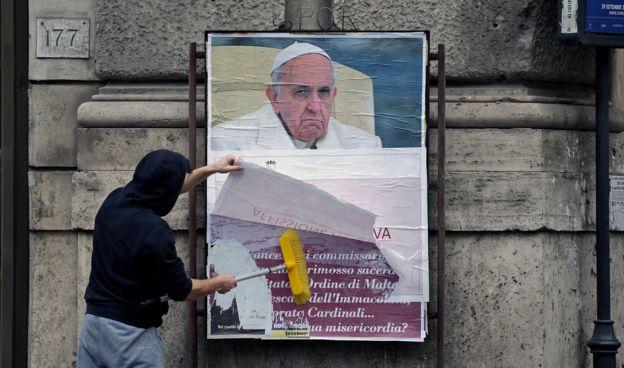 Un trabajador de la Alcaldía de Roma tapa uno de los carteles que cuestionan al Papa.