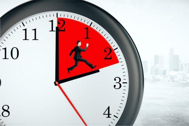 Hombre de negocios corre dentro de un reloj.