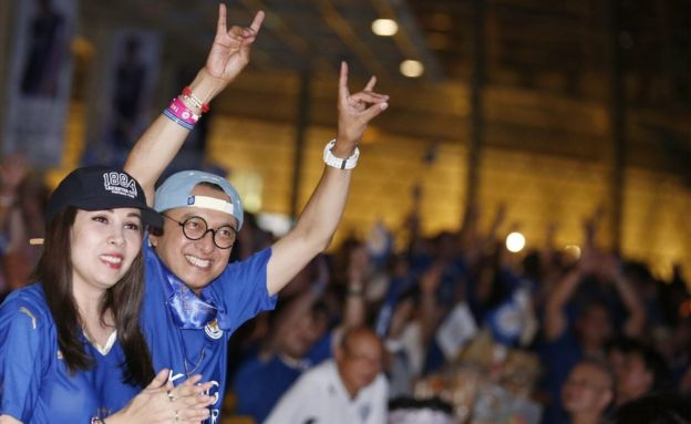 Two Thai supporters of Leicester City, two in the foreground and dozens behind, cheer while watching a match between Everton and Leicester, being shown outdoors in Bangkok