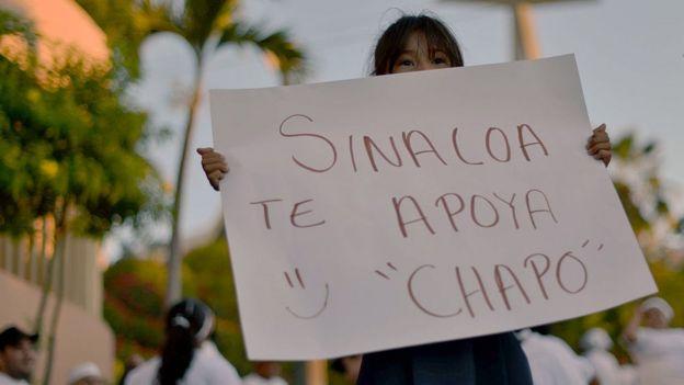 Una niña sostiene una pancarta que dice: