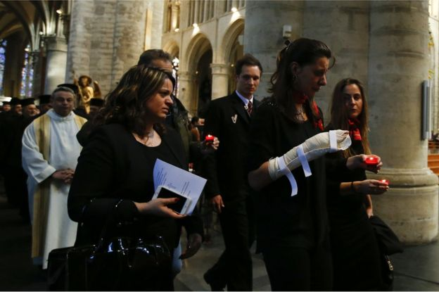 An injured airport worker caries a single candle as she walks in the procession during an ecumenical service for the victims of the Brussels bomb attacks at the Cathedral of St Michael and St Gudula in Brussels, 28 March