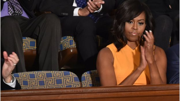 US First Lady Michelle Obama sits beside an empty chair (L) as her husband US President Barack Obama delivers his State of the Union address before a Joint Session of Congress