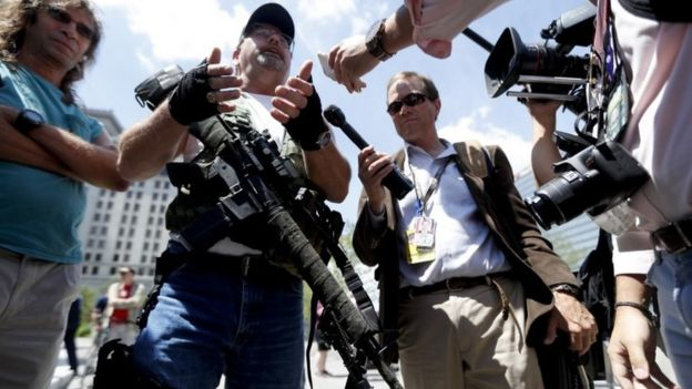 Second Amendment supporter Steve Thacker carries an AR-15-style weapon as he talks to the media during a protest