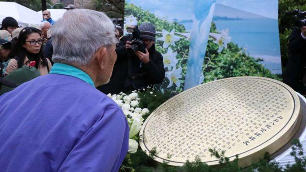 有受害者家属献完花后,仔细端详着二二八的纪念碑文