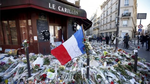 A French flag flies over flowers, candles and messages in tribute to victims outside Le Carillon restaurant, which was attacked on 13 November