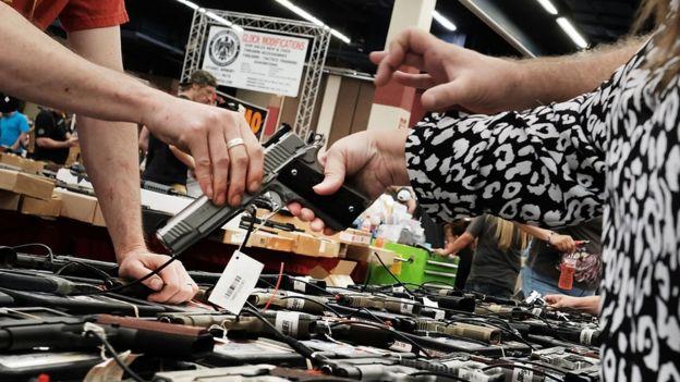 Una mujer sujeta un arma que le entrega otra persona en una feria en EEUU