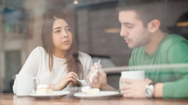 man and woman chatting over coffee and cake