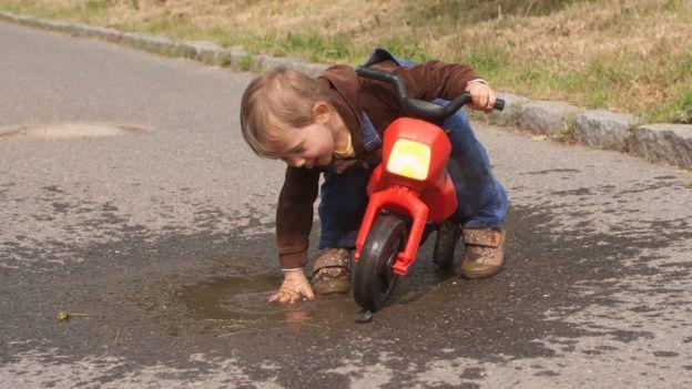 Niño juega con un charco de agua