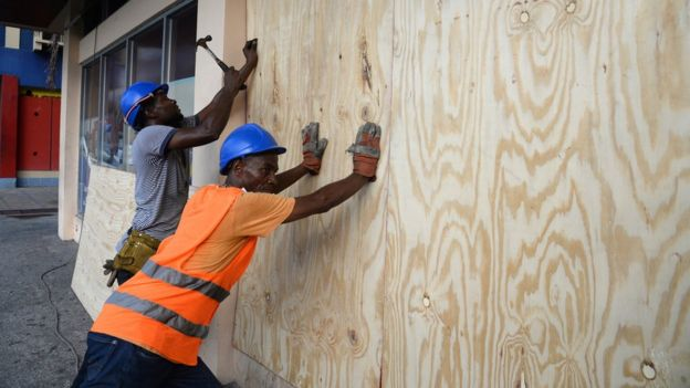 A worker nails a board to use on a storefront window as protection against hurricane Matthew in Kingston on 1 October